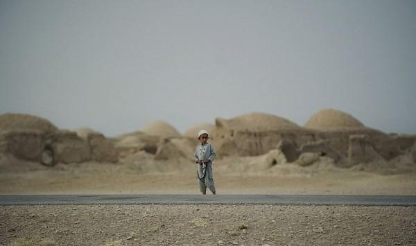 Афганский мальчик из племени Паштун смотрит, как соединенный патруль солдат 1-го взвода 1-64 танкового батальона армии США, находящийся под командованием НАТО, проходит через деревню Морган-Кеча в провинции Кандагар, 8 сентября 2012 года. (Тони Карумба / AFP Photo / Getty Images)