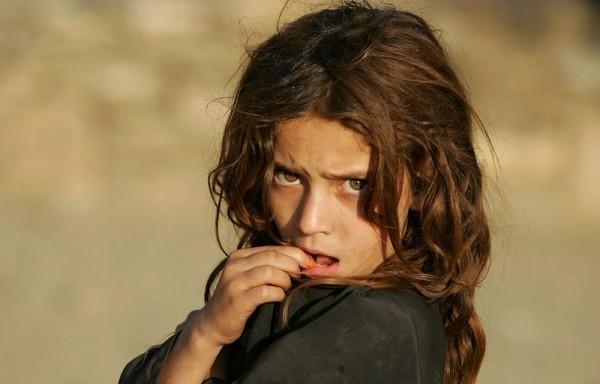 Девочка смотрит на американских солдат 1-го батальона 32 управления 10-й горной дивизии, патрулирующих рядом с базой Флорида в восточном Афганистане, 7 сентября 2006 года. (AP Photo / Саураб Дас)