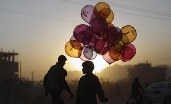 Магфуз Багбах, 12 лет, стоит у дороги, надеясь продать воздушные шарики на закате в Кабуле, 18 октября 2011 года. (AP Photo / Мухаммед Мухейзен)