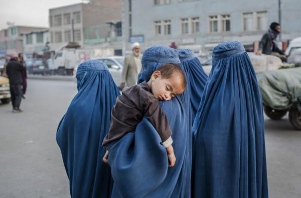Маленький мальчик спит на плече женщины в Старом Городе, 7 ноября 2012 года в Кабуле. (Даниэль Берулак / Getty Images)