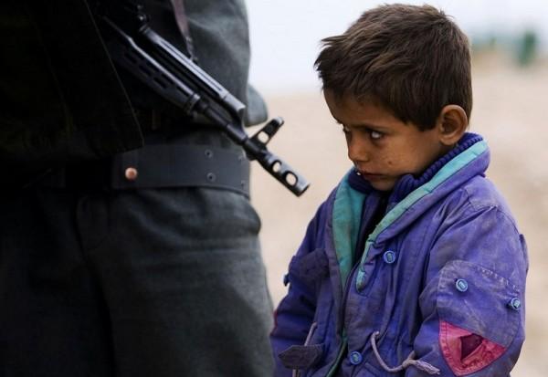 Афганский мальчик смотрит, как его отца обыскивает полицейский на контрольно-пропускном пункте района Деларам, провинции Нимроз, 21 января 2010 года. (Рейтер / Марко Джурика)