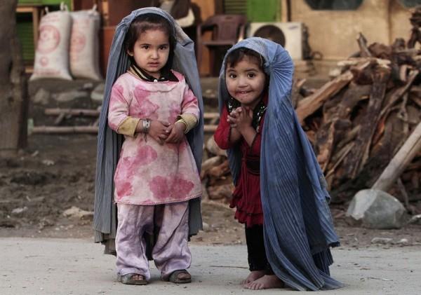 32.Две маленькие девочки играют в дом, подражая своим мамам, носящим паранджу. Паранджа подрезана под рост девочек. Пригород Джалалабада, восток Кабула, 17 марта 2013 года. (AP Photo / Рамат Гул)