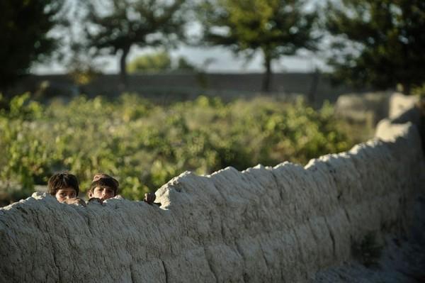 Два афганских мальчика наблюдают за солдатами армии США 3 взвода, компании С, 1-23 пехотного полка, патрулирующими деревню Генрандаи района Панжвай, 24 сентября 2012 года. (Тони Карумба / AFP Photo / Getty Images)
