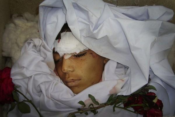 Тело афганского мальчика на похоронной процессии за городом Кост, Афганистан, , 24 ноября 2009 года. Дистанционно управляемая мина, спрятанная в баке с водой, взорвалась в пригороде Кост, в результате чего погибло шесть человек, среди которых было четверо детей, и был ранен еще один человек, по официальным данным и по словам родственников. Все жертвы были членами одной семьи, отправившейся за покупками к грядущему мусульманскому празднику Эйд. (AP Photo / Нишануддин Хан)