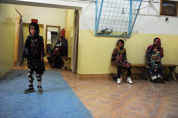 Девочка с ампутированными ногами пытается ходить на протезах в госпитале Международной комиссии Красного Креста для жертв войны и инвалидов в городе Мазер и Шариф, 1 мая 2013 года. (Фаршад Усян / AFP / Getty Images)