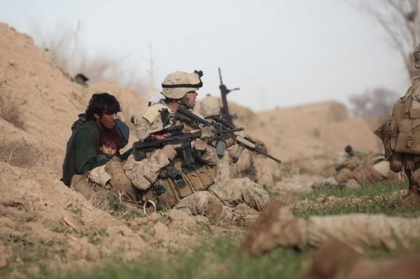 Американские солдаты морской пехоты и з компании Браво, 6-ая морская пехота - младший капрал Крис Сандерсон (сзади) и сержант Тревис Доусон (спереди) защищают афганского мужчину с ребенком от боевиков Талибана, открывших огонь в городе Марджа, провинции Гельманд, 13 февраля 2010 года. Войска НАТО под командованием США пошли в нападение на последнюю большую крепость Талибана в Афганистане, одной из самых горячих провинций, и боевики быстро открыли огонь. (Рейтер / Горан Томашевич)