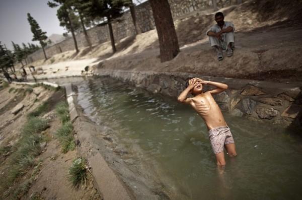 Афганский мальчик закрывает руками глаза и падает назад спиной в ручей в Кабуле, 10 августа 2011 года. (Рейтер / Ахмад Масуд)