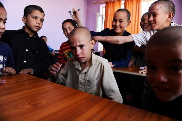 Афганский мальчик плачет, пока другие сироты дразнят его в классе приюта Балк на окраине города Мазар и Шариф, 7 октября 2012 года. 58 детей, преимущественно мальчиков, живут здесь. Их тут кормят, обучают и воспитывают при поддержке и по указаниям афганского правительства. (Кваис Усян / AFP / Getty Images)
