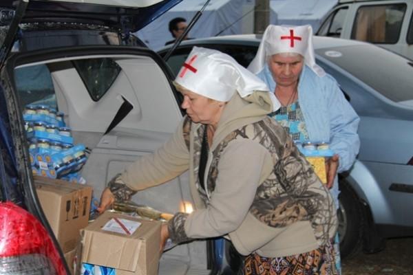 Сестры милосердия выгружают гуманитарную помощь Церкви палаточному лагерю возле города Донецк