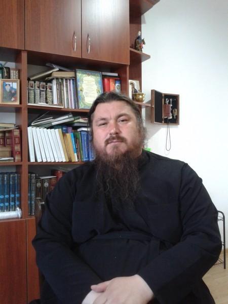 Иерей Сергий Дмитриенко - руководитель приюта Отрада. В шкафу на заднем плане - армейские фото ребят.