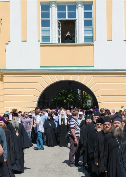 Патриарх Кирилл выходит из ворот монастыря в колонне крестного хода.