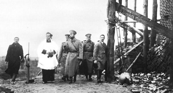 Император Николай II, католический священник и сопровождающие их лица в районе боевых действий. 1915. Вид братских могил первой мировой войны.