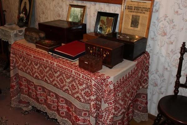 Стол с различными подарками и святынями, застеленный вышитой княгиней Шаховской скатерью