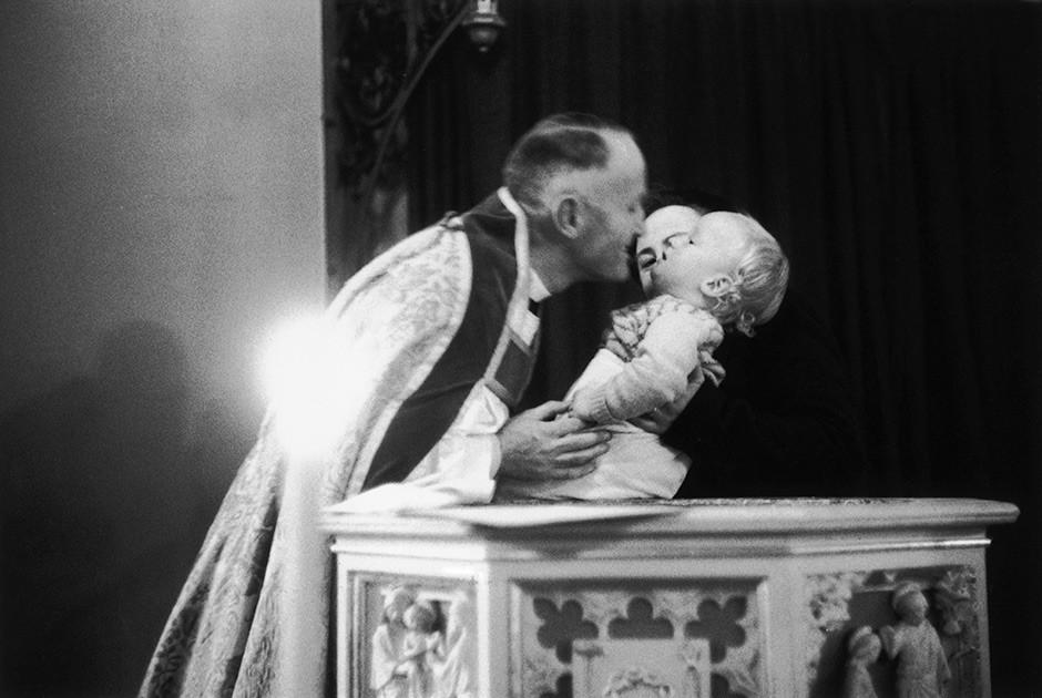 Thurston Hopkins / Picture Post / Getty Images / Fotobank 25 декабря 1954 года. Англиканский епископ Рэверенд Джордж Рэйндорп крестит ребенка в церкви Святого Стефана в Лондоне