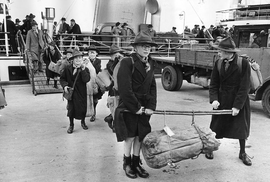 Thurston Hopkins / Picture Post / Getty Images / Fotobank 1955 год. Отряд скаутов с походным снаряжением сходит с парома в шотландском Бродике на острове Арран. Поселок Бродик — главное туристическое местечко острова с замком XV века, живописными холмами, озерами и реками.