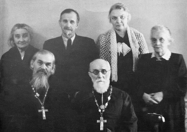 Сидят слева направо: протоиерей Клеоник Вакулович, протоиерей Александр Державин. Стоит первая слева Мария Владимировна Михайловская.
