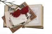 album with Vintage photos and two Red carnation flowers on white