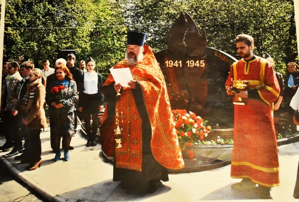 Священник освящает новый памятник