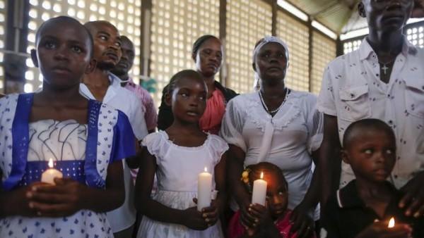 Кенийские христиане держат в руках свечи, вознося воскресные молитвы в католической церкви в Гариссе за души 148 человек, погибших во время нападения на университет Гарисса группировкой боевиков-исламистов Шабаб. (Даи Курокава /агентство European Pressphoto).