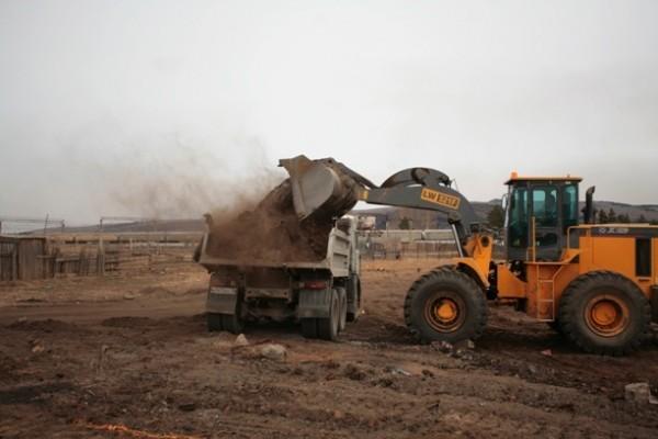 Остатки сгоревших домов уже расчищают и вывозят с помощью тяжелой техники
