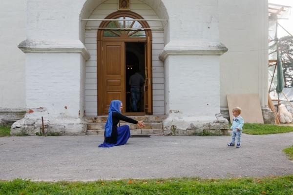 Однако храм продолжает работать: на фото - женщина с сыном после Крещения