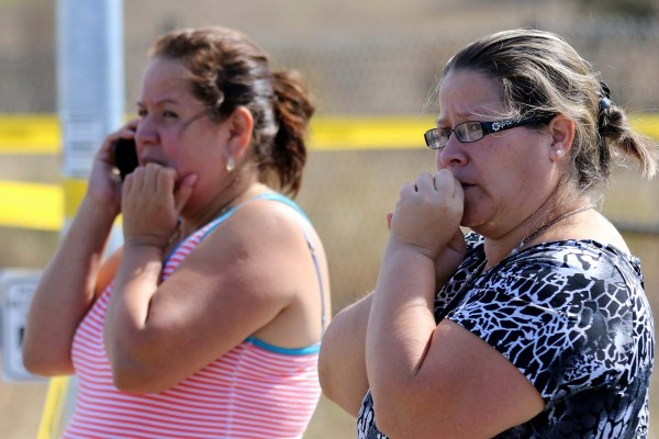 Two woman wait outside Umpqua Community College campus after a shooting at the school in Roseburg, Ore., on Thursday, Oct. 1, 2015. (AP Photo/Ryan Kang)