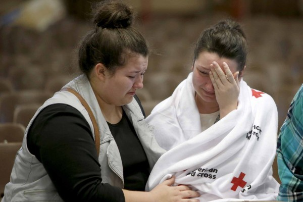 Hannah Miles, right, sits with her sister Hailey after Hannah was reunited with her family in Roseburg, Ore., on Thursday, Oct. 1, 2015, after a deadly shooting at Umpqua Community College. (Andy Nelson/The Register-Guard via AP) MANDATORY CREDIT