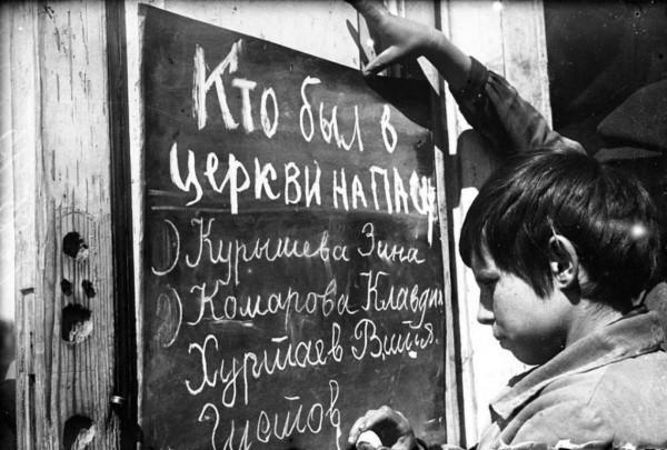 Школьники наносят на доску фамилии людей, пришедших в церковь на Пасху. Саратовская область. Фото:ТАСС