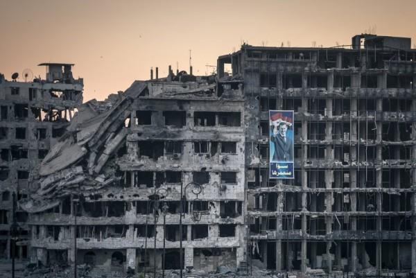 Плакат в поддержку Асада на разрушенном торговом центре в Хомсе,центр был построен, но так и не открылся. Сирия, 15 июня 2014-го. Для большинства сирийцев — это символ победы над боевиками сопротивления, но европейцы воспринимают это изображение с ровно противоположным смыслом