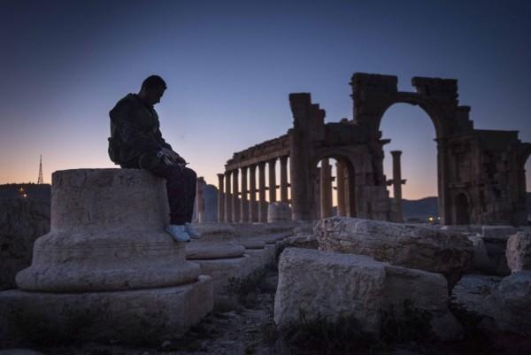 Солдат правительственных войск сидит на восточной части колоннады в разрушенной Пальмире