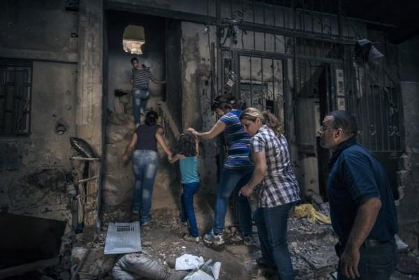 Семья поднимается по камням, которые остались от их брошенного два года назад жилища, чтобы проверить, пригодно ли оно для жизни