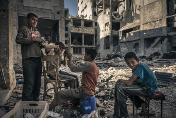 Сирийский дети играют, отдыхая в перерывах между сбором металлолома
