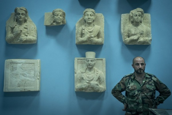 Солдат сирийской армии рядом со скульптурами в музее Пальмиры