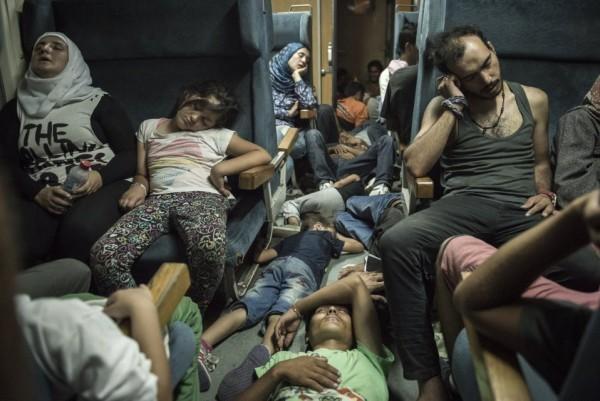 Беженцы спят в поезде, который везет их через Македонию от границы Сербии на юге до греческой границы на севере