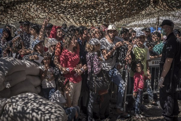 Беженцы стоят в очереди за документами в приемном центре для беженцев