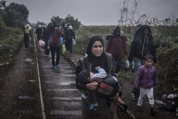 Женщина несет своего ребенка на руках, следуя по железнодорожным путям по направлении к венгерской границе вместе с другими мигрантами
