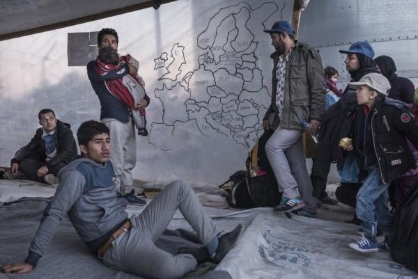 Мигранты стоят рядом с самодельной картой Европы в приемном центре для беженцев Мориа