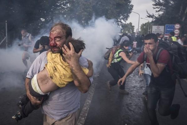 Мужчина пытается защитить сына от ударов и слезоточивого газа во время столкновения мигрантов с венгерской полицией, пытающейся закрыть границу