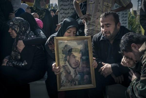 Родственники и работники похоронного бюро рядом с портретом солдата, погибшего во время битвы в Ярубе на кладбище для сирийских солдат в деревне Саеда Зайнаба