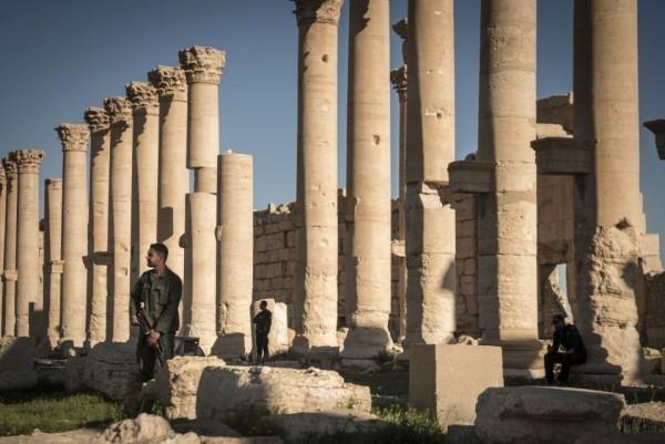 Солдаты службы внутренней безопасности смотрят на разрушенный храм Бела в Пальмире 30 августа 2015 года