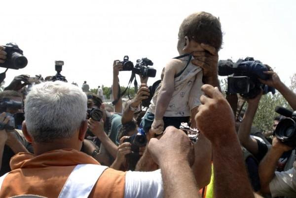 ©Jeroen Oerlemans/www.worldpressphoto.org  Врачи держат тело мальчика, погибшего под завалами жилого дома после воздушной атаки израильской армии.