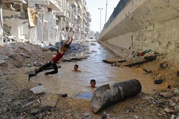 ©REUTERS Baz Ratner Сирия. Дети играют в яме с водой, образованной от взрыва в Алеппо.