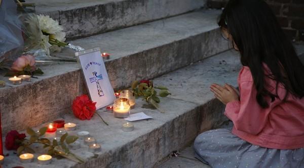 Девочка молится у дверей церкви, где был убит священник Жак Хамель. Фото: Pascal Rossignol/Reuters