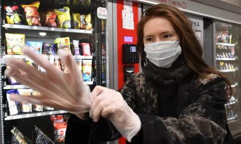 Девушка в маске надевает перчатки