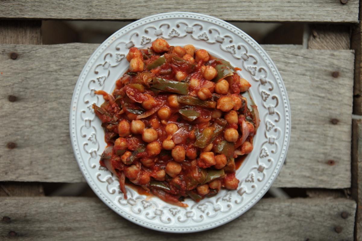 1. Порежьте лук полукольцами, болгарских перец ломтиками, мелко порубите чили. Чеснок раздавите плоской стороной ножа и мелко порежьте. Зелень порежьте. В кастрюле или сотейнике с толстым дном разогрейте на среднем огне оливковое масло. Добавьте болгарский перец, чили, лук, чеснок и готовьте, помешивая, пару минут, пока овощи не станут мягкими.  2. Откройте банки с нутом, жидкость слейте. Отправьте в кастрюлю помидоры и базилик, половину петрушки, приправьте солью и перцем. Накройте крышкой, убавьте температуру и тушите около 5 минут. Затем всыпьте горох нут и тушите еще 5 минут. Такое рагу можно подать с рисом, оно замечательно как холодным, так и горячим.